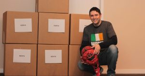 John Fitzgerald, Founder and Executive Director of the Baseball United Foundation, with a shipment of donated baseball equipment bound for Kenya.